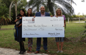 Mike Terrio presents Barbi with her $1,000 donation as part of The Ten Weeks of Charity.