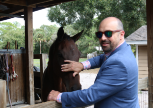 Mike Terrio pets a horse at Nala's New Life Rescue.